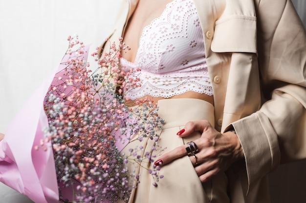 Gros plan sans tête femme en costume beige et soutien-gorge blanc tenir bouquet de fleurs séchées colorées manucure rouge deux anneaux sur les doigts