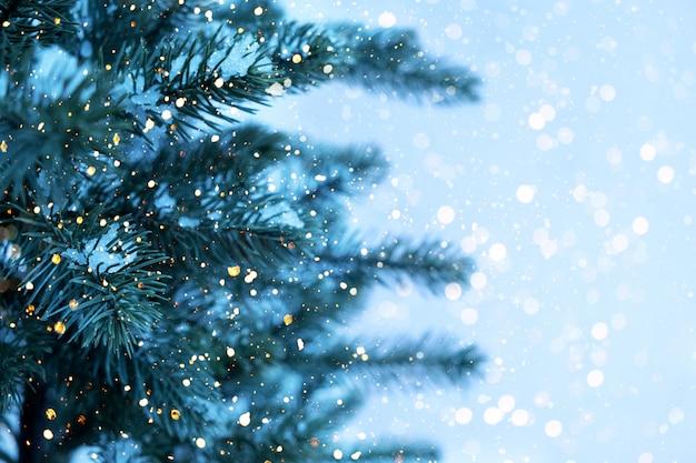Gros plan de sapin de noël avec lumière, flocon de neige. fond de vacances de noël et du nouvel an. ton de couleur vintage.