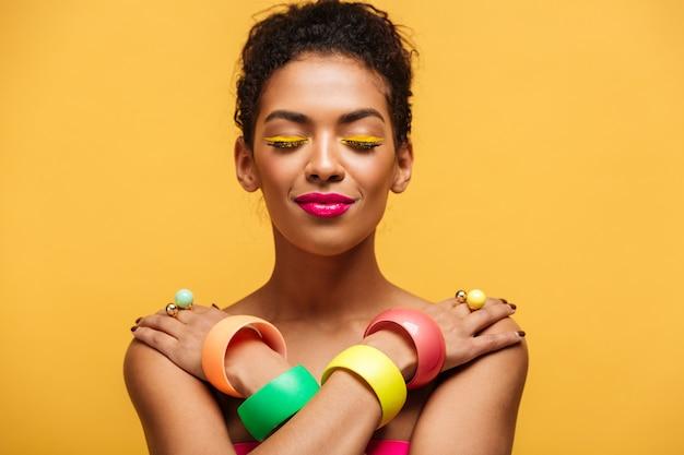 Gros plan satisfait femme mulâtre nue avec maquillage mode et accessoires posant sur l'appareil photo avec les mains croisées sur les épaules, sur jaune