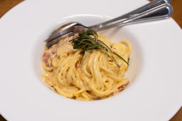 Gros plan de sauce spaghetti cabonara dans une assiette blanche sur une table en bois.