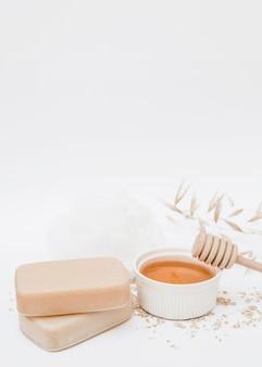 Gros plan de savon; mon chéri; louche de miel et luffa sur fond blanc
