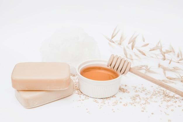 Gros plan des savons; mon chéri; louche de miel et luffa sur fond blanc
