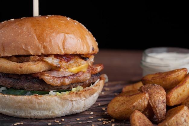 Gros plan d'un savoureux burger avec des collations.