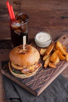 Gros plan d'un savoureux burger avec des snacks.