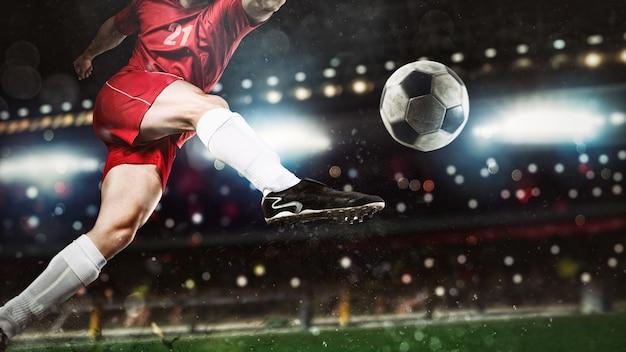 Gros plan d'une scène de football lors d'un match de nuit avec un joueur en uniforme rouge frappant le ballon avec puissance