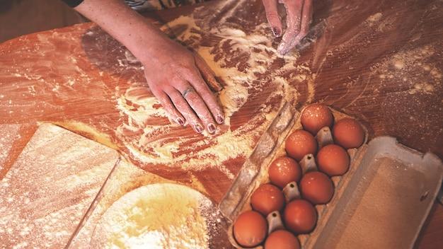 Gros plan sur la scène des mains féminines faisant de la pâte. flou artistique, cuisine, ingrédients de cuisine