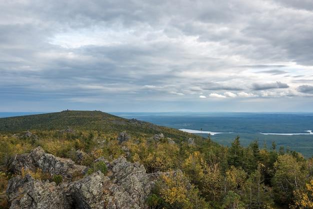 Gros plan des scènes de montagnes dans le parc national kachkanar, russie, europe. temps nuageux, ciel bleu dramatique, arbres verts lointains. journée d'été colorée