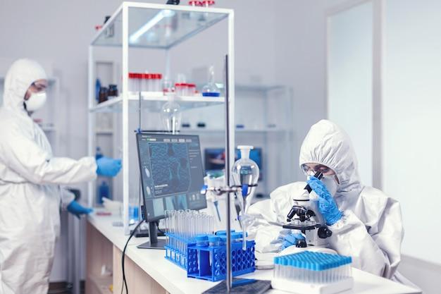 Gros plan d'un scientifique à l'aide d'un microscope un microscope portant un costume ppe dans un laboratoire équipé. chercheur chimiste pendant une pandémie mondiale avec un échantillon de contrôle de covid-19 dans un laboratoire de biochimie