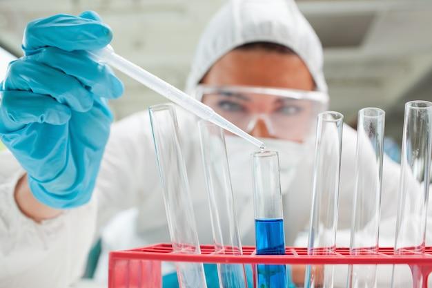 Gros plan d'un scientifique protégé laissant tomber le liquide dans un tube à essai
