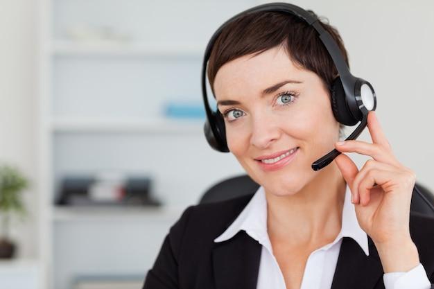 Gros plan d'une secrétaire souriante appelant avec un casque
