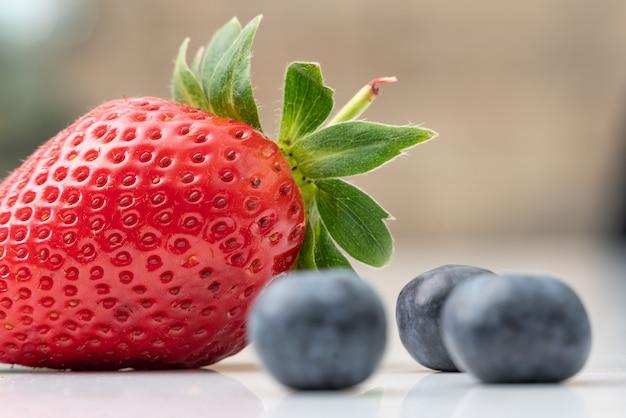 Gros plan sélectif de fraises mûres et de bleuets