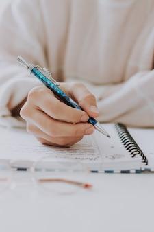 Gros plan sélectif vertical d'une femme écrivant dans un cahier avec un stylo bleu