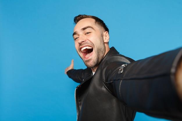 Gros plan selfie d'un jeune homme mal rasé élégant en t-shirt blanc en veste de cuir noir à la recherche d'une caméra isolée sur fond de mur bleu portrait en studio. concept d'émotions sincères de personnes. maquette de l'espace de copie