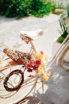 Gros plan de la selle de vélo avec des fleurs colorées et connectez-vous sur le tronc