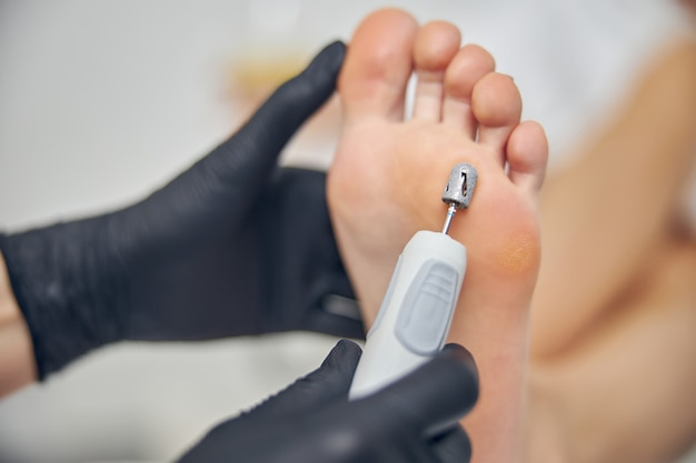 Gros plan sur la semelle du pied féminin pendant que l'esthéticienne porte des gants stériles noirs à l'aide d'une machine à éplucher