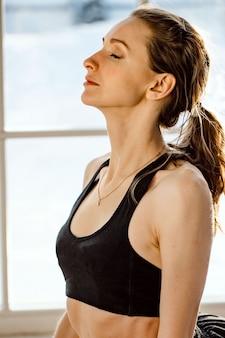 Gros plan sereine jeune femme prenant une profonde respiration d'air frais relaxant en méditant les yeux fermés.