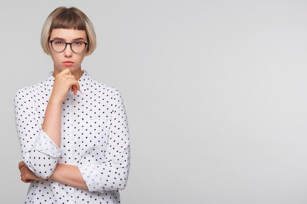 Gros plan de sérieuse belle jeune femme blonde porte une chemise à pois