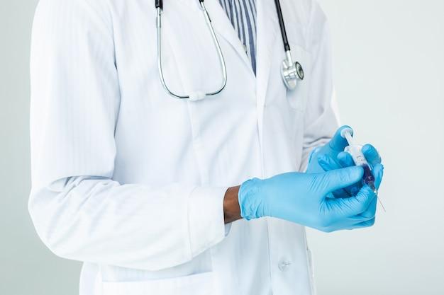 Gros plan de la seringue dans les mains d'un médecin expérimenté se préparant à l'injection