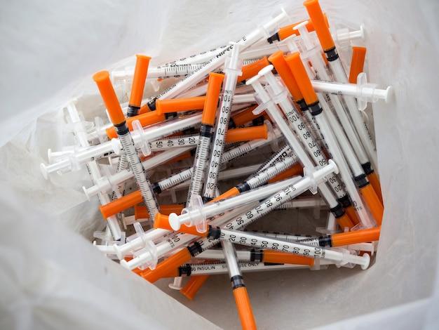 Gros plan des seringues usagées à la poubelle