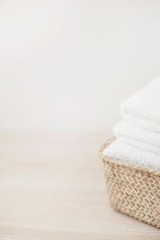 Gros plan de serviettes blanches dans le panier sur une table en bois