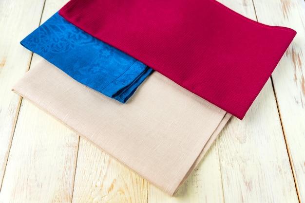 Gros plan de serviettes en tissu de couleurs beige, bleu et bordeaux sur table en bois blanc rustique. faible profondeur de champ.