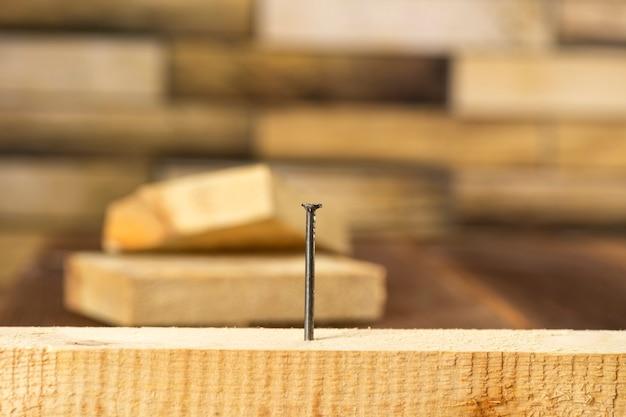 Gros plan d'un seul clou coincé dans une planche de bois