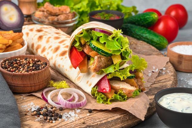 Gros plan de shawarma sur un mur gris avec des ingrédients. fast food. vue latérale, gros plan.