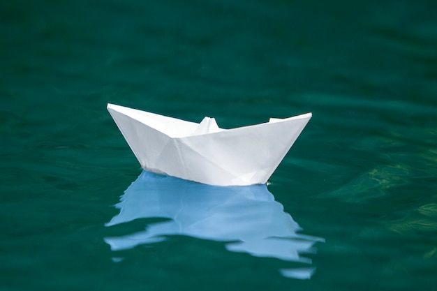 Gros plan, simple, petit, blanc, origami, papier, bateau, flotter, tranquillement, bleu, clair, rivière, eau mer, sous, clair, été, ciel concept de liberté, de rêves et de fantasmes, fond.