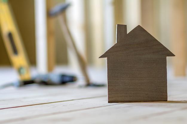 Gros plan d'une simple petite maison modèle brune sur fond d'outils de construction floue. construction, construction et investissements dans l'immobilier, la propriété et la propriété du concept de maison de rêve.