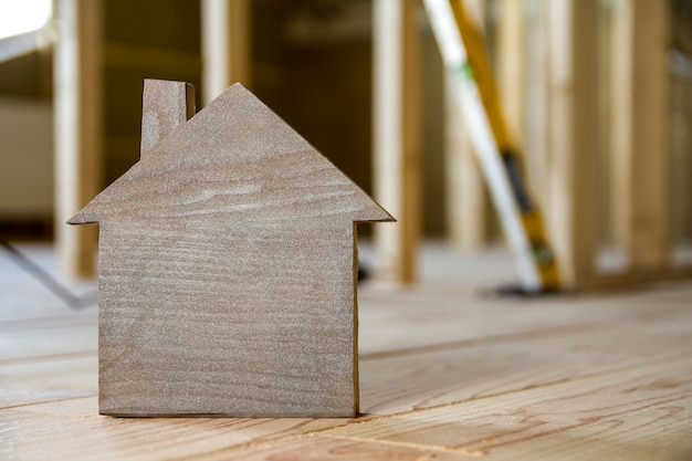 Gros plan d'une simple petite maison modèle brune sur des outils de construction floue. construction, construction et investissements dans l'immobilier, la propriété et la propriété du concept de maison de rêve.