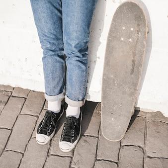 Gros plan, de, skateur, pieds, à, skateboard, debout, devant, mur
