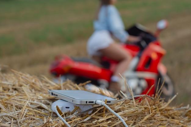 Gros plan sur un smartphone avec un chargeur portable. power bank charge le téléphone dans le contexte d'une moto, d'une fille et de la nature.