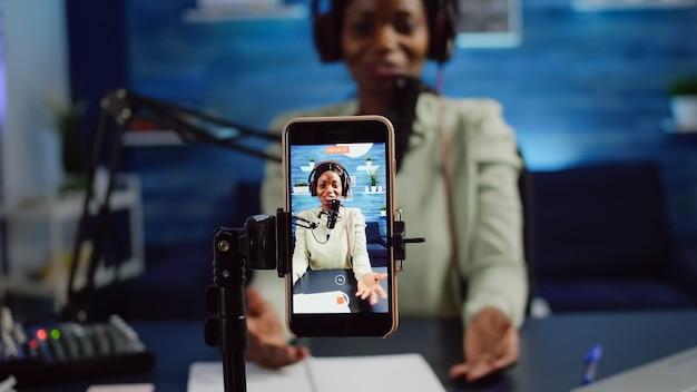 Gros plan sur un smartphone enregistrant une influenceuse de femme noire qui parle pendant un podcast en ligne