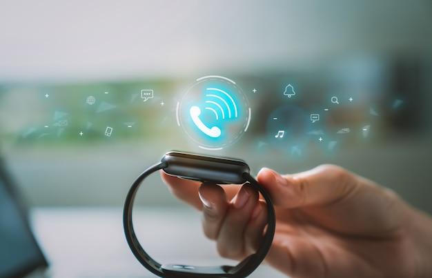 Gros plan sur une smartwatch touchant la main avec une application d'appel avec une icône sociale à l'écran, un gadget pour un mode de vie actif.