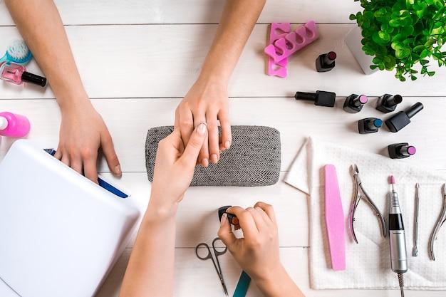 Gros plan sur les soins des ongles des mains féminines classant les ongles avec une lime à ongles professionnelle dans le haut du salon de manucure de beauté ...