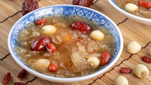 Gros plan de la soupe aux champignons blanche neige douce traditionnelle chinoise avec des graines de lotus, des dattes rouges (jujube) et goji berry (goji berry, gojiberry) sur blanc
