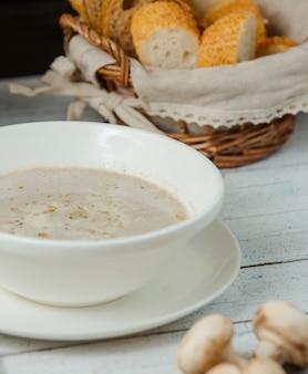 Gros plan de soupe aux champignons dans un bol servi avec du pain