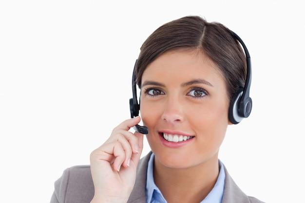 Gros plan de souriant agent de centre d'appel féminin en ajustant son casque