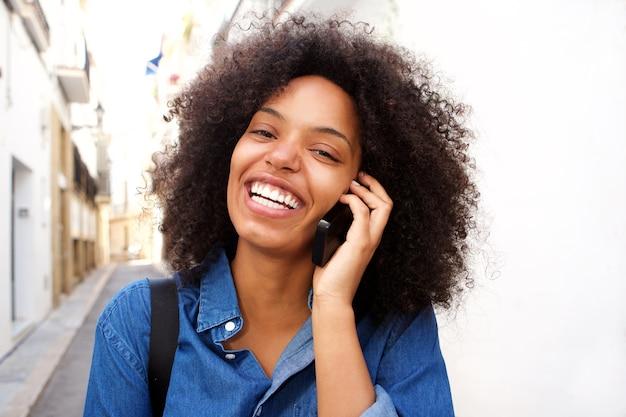 Gros plan souriant femme afro-américaine parlant au téléphone intelligent