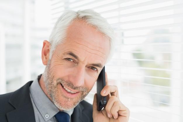 Gros plan de souriant homme d'affaires mature à l'aide de téléphone portable