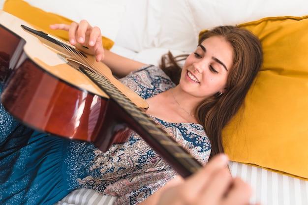 Gros plan, de, sourire, adolescente, coucher lit, jouer guitare