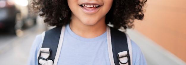 Gros plan de sourire d'enfant, retour à l'école