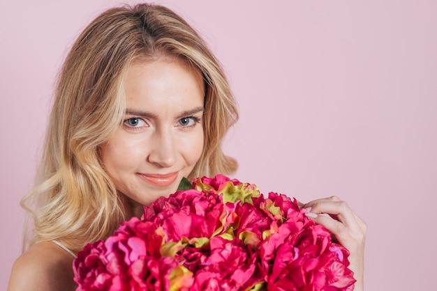 Gros plan, de, sourire, jeune femme, tenant, bouquet fleur rose