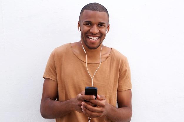 Gros plan, sourire, noir, homme, à, écouteurs, et, téléphone portable, debout, contre, mur blanc