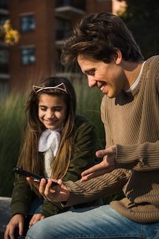 Gros plan, de, sourire, père, et, fille, regarder, téléphone intelligent