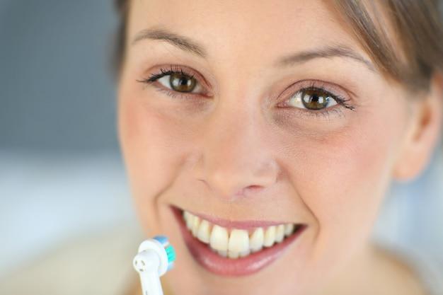 Gros plan sur le sourire à pleines dents de la femme se brosser les dents