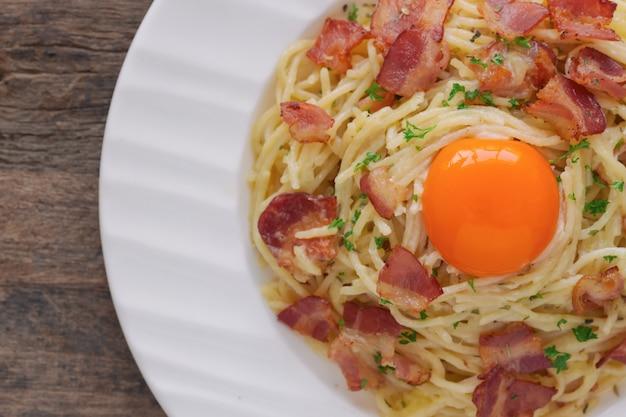 Gros plan spaghetti carbonara sur table en bois