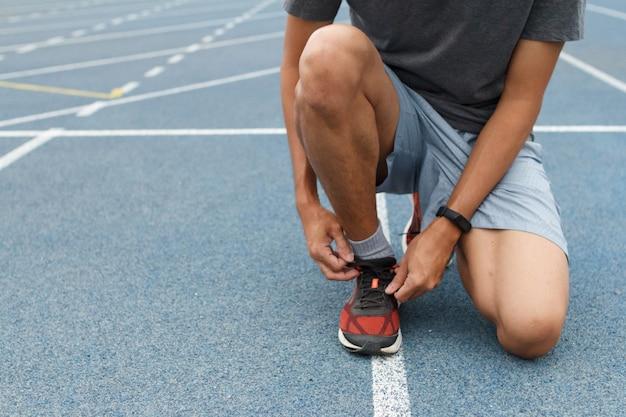 Gros plan, sportif, bleu, courant, piste, stade il attache des baskets sur des chaussures de course avant de s'entraîner. concept en cours d'exécution.