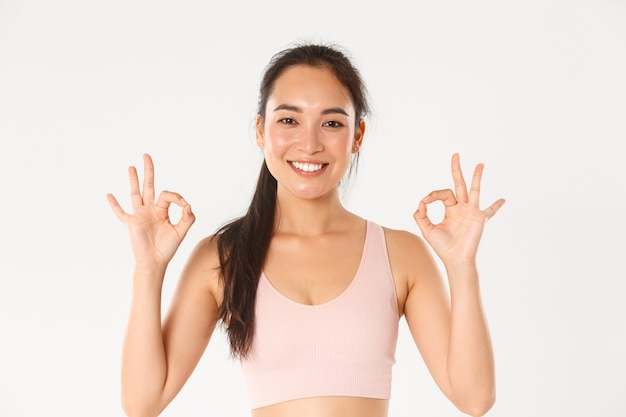 Gros plan d'une sportive asiatique souriante et satisfaite recommande des cours de gym ou de yoga, montrant un geste correct, satisfaite d'un entraîneur en ligne parfait.