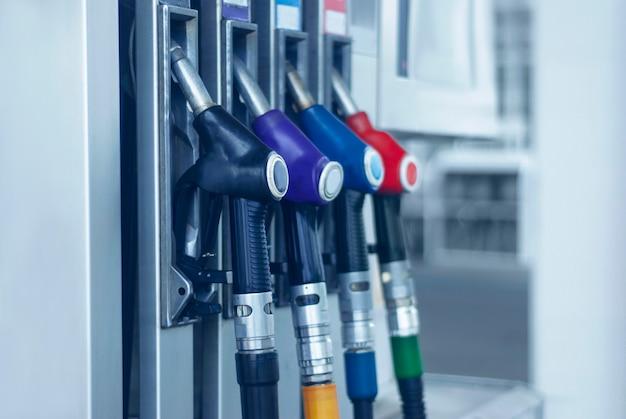 Gros plan de station d'essence avec des tuyaux de carburant colorés.